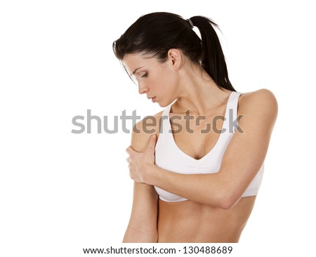 beautiful brunette is having a pain in her shoulder - stock photo