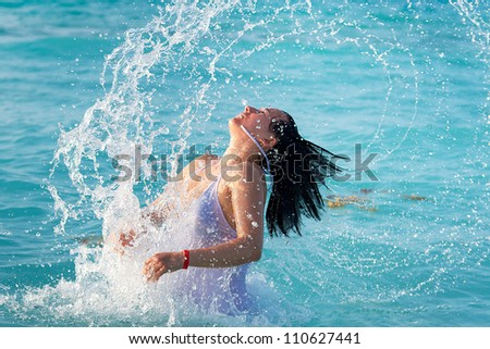 Beautiful brunette jumping out of the Caribbean Sea - stock photo