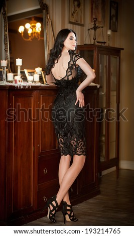Beautiful brunette lady in elegant black lace dress posing in a vintage scene. Young sensual  fashionable woman on high heels in luxurious scenery near lighting candles reflected in large mirror. - stock photo