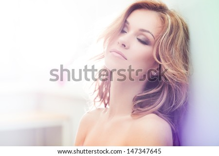 Beautiful brunette lady posing in bleached light - stock photo
