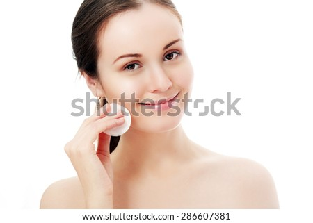 Beautiful brunette lady removing makeup from her face, skin care concept / photoset of attractive brunette girl on white background  - stock photo