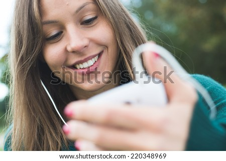 beautiful brunette lady touching and browsing her smart phone  - stock photo