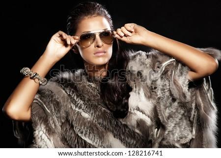 Beautiful brunette lady wearing fur and sunglasses. Fashionable photo. - stock photo