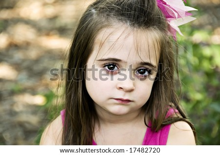 Beautiful brunette little girl posing with a sad facial expression. - stock photo