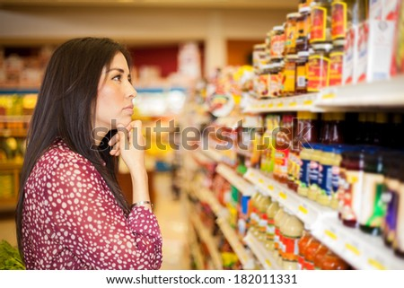Beautiful brunette looking at some shelves in a supermarket trying to decide what to buy - stock photo