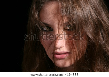 Beautiful brunette looking scary out of her wolf eyes on black background - stock photo