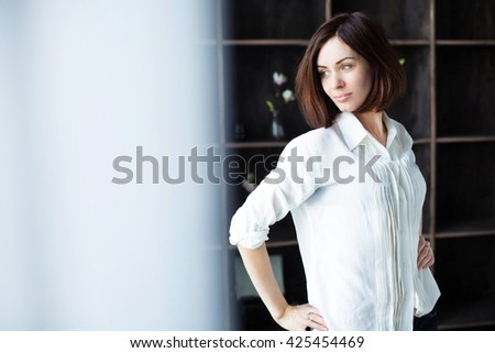 beautiful brunette looks out the window - stock photo