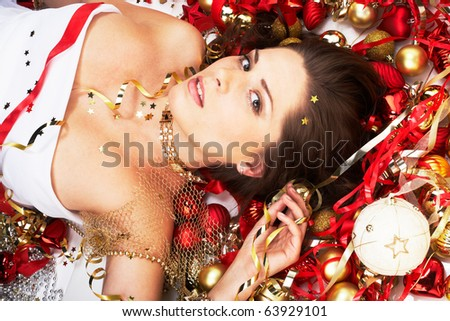 Beautiful brunette lying among Christmas decoration