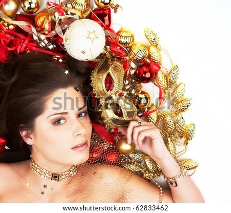 Beautiful brunette lying among Christmas decoration holding mask isolated on white - stock photo