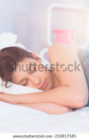 Beautiful brunette lying on bed sleeping at home in the bedroom - stock photo