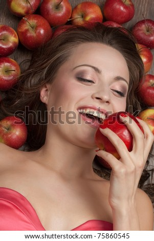 Beautiful brunette lying on the floor and biting a red apple, surrounded by apples - stock photo