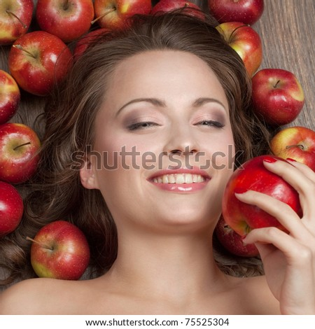 Beautiful brunette lying on the floor surrounded by apples and keeps one in his hand - stock photo