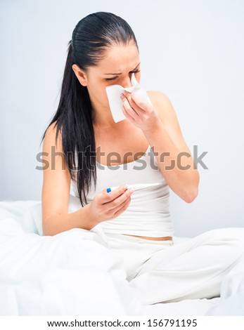 beautiful brunette measures the temperature of a sick - stock photo