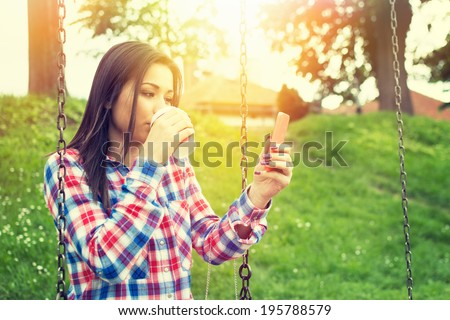 Beautiful brunette mixed race teenage girl in park with smartphone and takeaway coffee enjoying relaxing on sunny summer day.  - stock photo