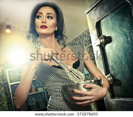 Beautiful brunette mixing ingredients in a bowl. Sensual slim young woman with black bra and low cut neck baking in a professional kitchen. Attractive lady with makeup cooking holding a whisk  - stock photo