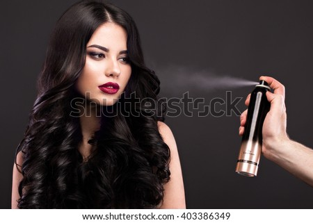 Beautiful brunette model: curls, classic makeup and red lips with a bottle of hair products. The beauty face.  - stock photo