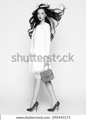 Beautiful brunette model in fashion clothes posing in studio. Black and white photo - stock photo