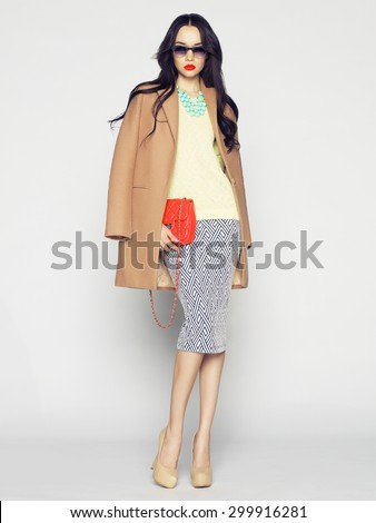 Beautiful brunette model in fashion clothes posing in studio. Wearing coat, handbag, shoes - stock photo