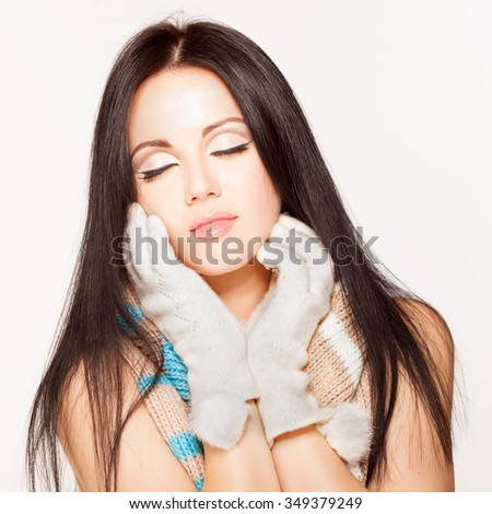 Beautiful brunette model in knit scarf and gloves. Winter clothes. Closed eyes/