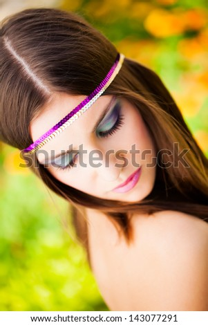 beautiful brunette model with a purple and gold headband looking over her naked shoulder in the park