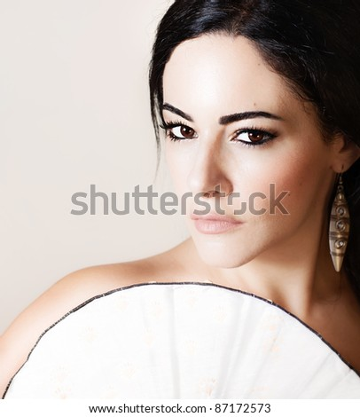 Beautiful brunette model with Chinese fan, closeup female portrait isolated on beige background - stock photo