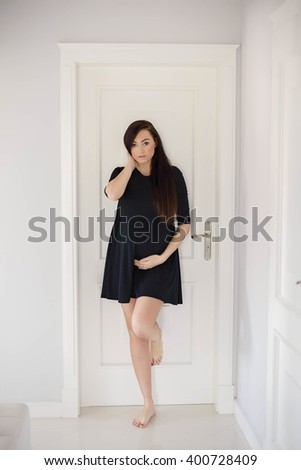 Beautiful brunette 8 months pregnant woman posing in home hall. Dressed in black dress - stock photo