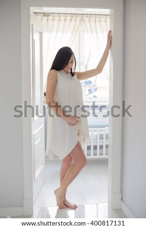Beautiful brunette 8 months pregnant woman posing in home hall near child room with white crib. Dressed in white dress - stock photo