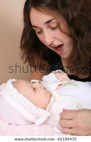 Beautiful brunette mother looking at her two month old baby girl