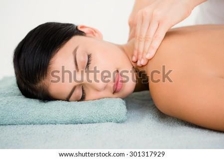 Beautiful brunette on a massage table at spa center - stock photo