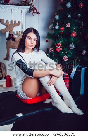 Beautiful Brunette on the Background of New Year's decoration. Fashion Beauty Portrait. Sexy Girl. Holiday Makeup - stock photo