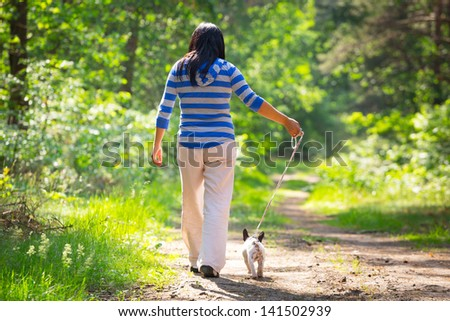 Beautiful brunette on the walk with the dog - stock photo