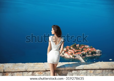 Beautiful brunette over blue sky posing in white dress. holidays, vacation, travel. Sveti Stefan island in Budva. Montenegro.