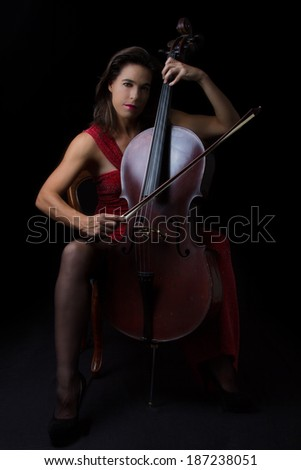 Beautiful brunette playing a cello with selective light in red dress - stock photo