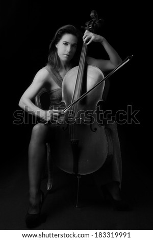 Beautiful brunette playing a cello with selective light in red dress artistic conversion - stock photo