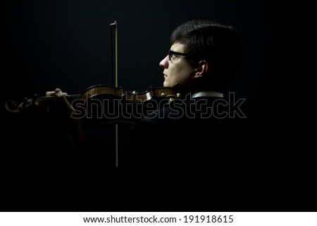 beautiful brunette plays the violin in the dark