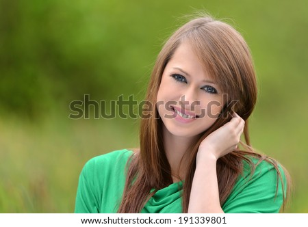 beautiful brunette posing against fresh green background - stock photo