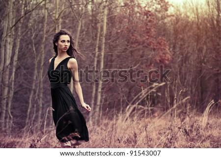 beautiful brunette posing in a field - stock photo
