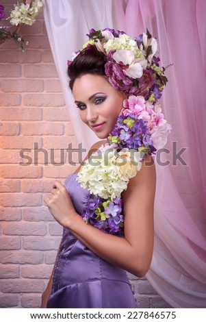 Beautiful brunette posing in floral decorations - stock photo