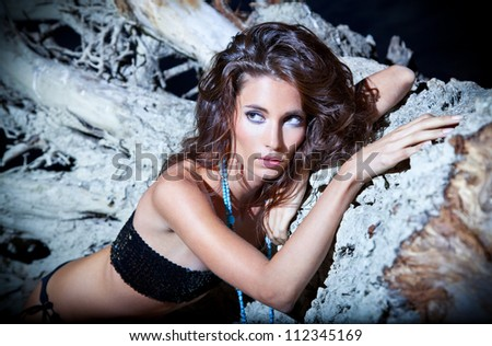 Beautiful brunette posing  on river bank. Night Art photo. - stock photo