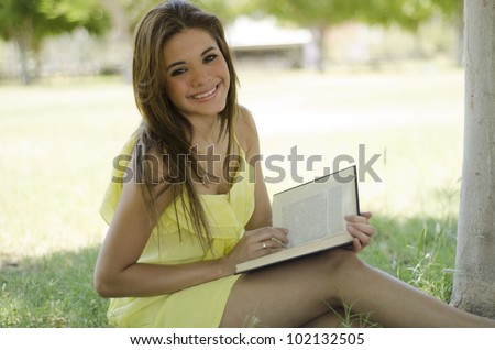Beautiful brunette reading and relaxing at the park