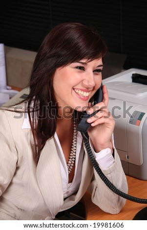 Beautiful brunette receptionist talking on the telephone