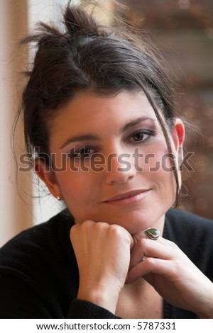 Beautiful brunette relaxing in front of the window - stock photo