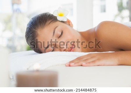 Beautiful brunette relaxing on massage table at the health spa