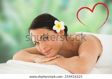 Beautiful brunette relaxing on massage table smiling at camera against heart - stock photo