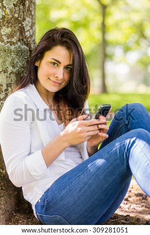 Beautiful brunette sending text in the park on a sunny day