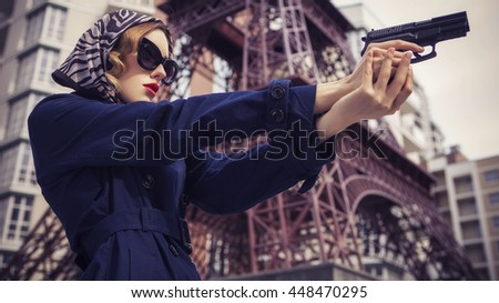 Beautiful brunette sexy spy agent (killer or police) woman in jacket and sunglasses with a gun in her hand running someone, to catch him in a european city