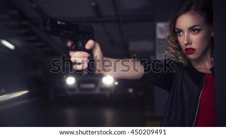 Beautiful brunette sexy spy agent (killer or police) woman in leather jacket and jeans with a gun in her hand running after someone, to catch him on parking - stock photo