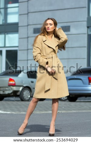 Beautiful brunette shows fashionable black coat on the background of the spring streets cape - stock photo