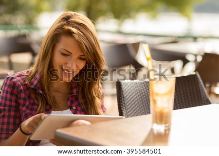 Beautiful brunette sitting in an outdoor cafe, reading an e-book on her tablet computer and drinking lemonade - stock photo