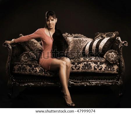 beautiful brunette sitting on sofa - stock photo